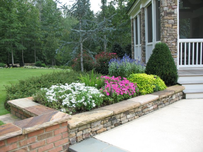A flower bed consisting of colorful annuals behind a stacked stone wall in Alpharetta Georgia