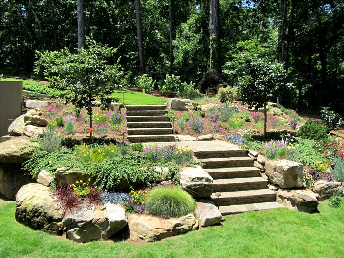 A bluestone stairway supported by large boulders and surrounded by perennial gardens