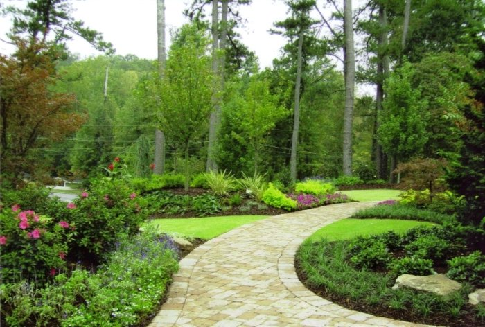 A curving concrete paver pathway surrounded by gardens of perennials, shrubs and small trees.