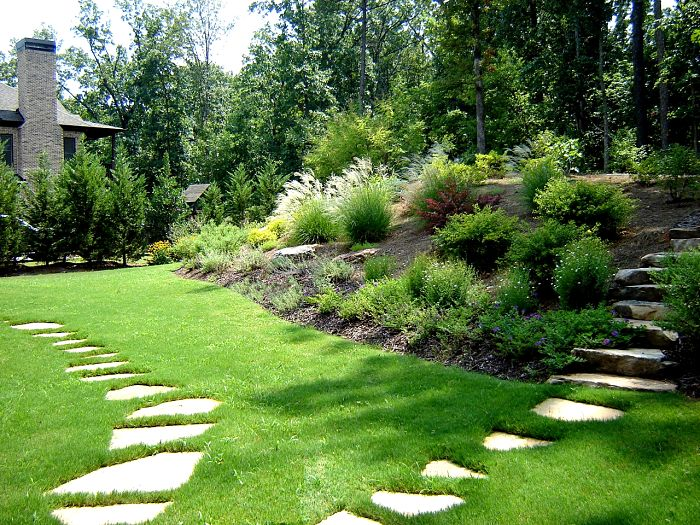 A backyard landscape in Marietta Georgia with irregular flagstone steppers, a bermuda lawn, and a garden of flowering perennials and shrubs on a slope.