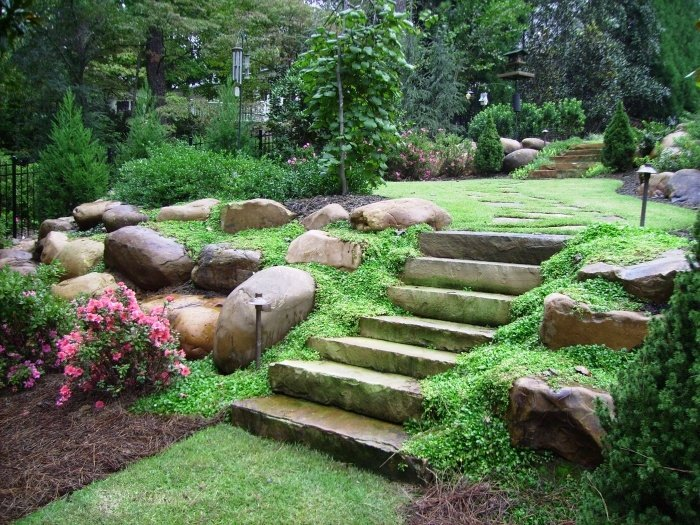 A backyard landscape in the Buckhead section of Atlanta with flagstone slab steps, boulders, and mazus groundcover in the foreground