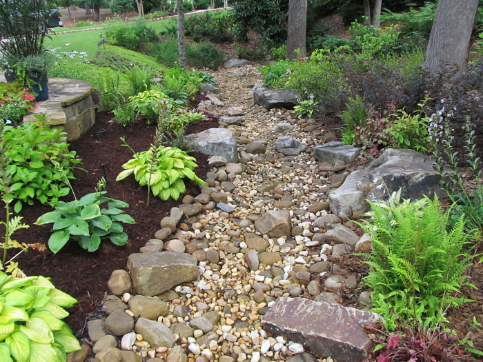 A dry creek bed, consisting of various sizes of pebbles, river rock, and boulders, and surrounded by a perennial garden