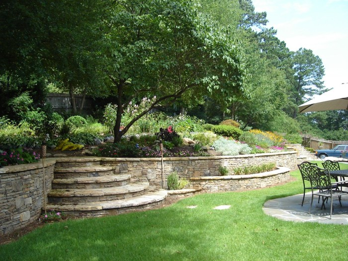 A stacked stone retaining wall in Lilburn Georgia with curved stone steps, built-in planters, and perennial gardens next to an Eastern Redbud tree