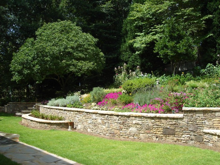A backyard landscape with a stacked stone retaining wall having curved steps and built-in planters, and perennial flower gardens.