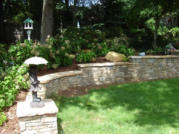 A stepped, stacked stone retaining wall with a hydrangea garden in Lilburn Georgia