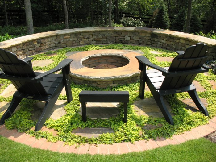A stacked stone firepit with flagstone cap, surrounded by flagstone steppers and creeping jenny ground cover in Alpharetta Georgia