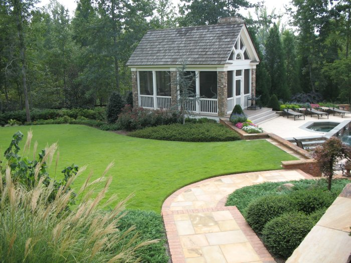 Backyard landscaping consisting of a flagstone walkway with brick border, zoysia lawn, pool house, and gardens with mostly evergreen shrubs